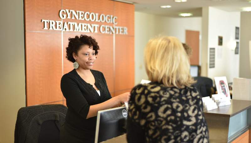 A desk attendant helps a woman at the Gynecologic Treatment Center