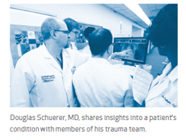 Douglas Schuerer, MD, shares insights into a patient's condition with members of his trauma team.